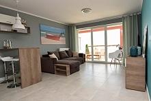 Widok na aranżację przestrzeni salonu, wykonanego w ramach projektowania wnętrza nadmorskiego apartamentu w Darłówku. Salon ma nowoczesny i prosty styl, który pasuje do preferen...