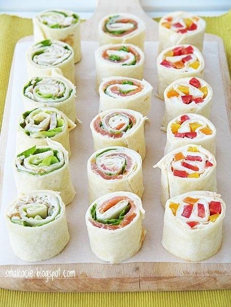 """Roladki z kurczakiem, sałatą i majonezem (6 sztuk)  Składniki: - 1 tortilla pszenna (gotowa lub domowa) - usmażony lub upieczony pojedynczy filet z kurczaka - na 1 tortillę spokojnie wystaczy połowa - 3 liście sałaty - majonez  Przygotowanie: Tortillę posmaruj dokładnie majonezem. Zostawiając wolne miejsce na jednym końcu rozłóż liście sałaty a następnie pokrojony w cienkie plasterki filet. Ważne żeby składniki były rozłożone równomiernie i tworzyły niezbyt grubą warstwę. Możesz z sałaty powykrawać nasady liści. Zawijaj w ciasny rulon. Pozostawiony na końcu fragment z majonezem pozwoli zlepić rulon. Z końców rolady odkrój po 1 cm, a następnie pokrój ją ostrym nożem na 6 kawałków.   Roladki z kremowym twarożkiem, wędzonym łososiem i rukolą (6 sztuk)  Składniki: - 1 tortilla pszenna (gotowa lub domowa) - kremowy twarożek do kanapek - naturalny - ok. 70 g wędzonego łososia - mała garść rukoli  Przygotowanie: Tortillę posmaruj dokładnie kremowym twarożkiem.. Zostawiając wolne miejsce na jednym końcu rozłóż łososia, a następnie liście rukoli. Ważne żeby składniki były rozłożone równomiernie i tworzyły niezbyt grubą warstwę. Zawijaj w ciasny rulon. Pozostawiony na końcu fragment z twarożkiem pozwoli zlepić rulon. Z końców rolady odkrój po 1 cm, a następnie pokrój ją ostrym nożem na 6 kawałków.  Roladki z kremowym twarożkiem i papryką (6 sztuk)  Składniki: - 1 tortilla pszenna (gotowa lub domowa) - kremowy twarożek do kanapek - papryka świeża w kilku kolorach (u mnie żółta, pomarańczowa i czerwona) - po kilka """"pasków"""" z każdego koloru  Przygotowanie: Tortillę posmaruj dokładnie kremowym twarożkiem.. Zostawiając wolne miejsce na jednym końcu rozłóż paprykę tak aby kolory się wymieszały. Zawijaj w ciasny rulon. Pozostawiony na końcu fragment z twarożkiem pozwoli zlepić rulon. Z końców rolady odkrój po 1 cm, a następnie pokrój ją ostrym nożem na 6 kawałków.  Roladki podawaj od razu lub do czasu podania przechowuj w lodówce owinięte folią, aby nie wyschły."""