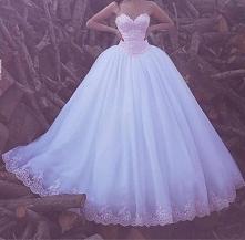 Suknia ślubna z różowym gorsetem z dekoltem w serce i białą rozkloszowaną spódnicą mającą na dole różową koronkę.