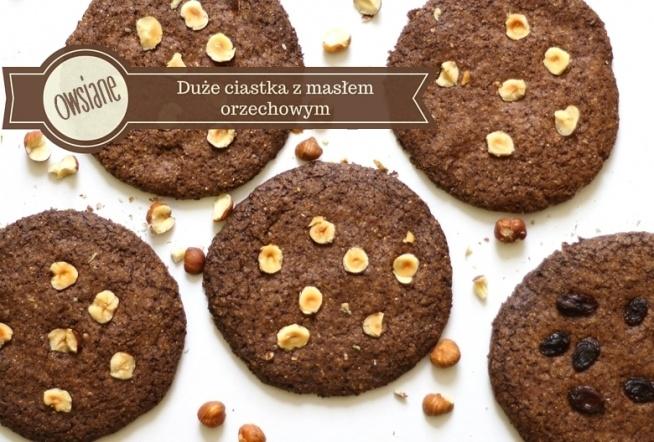 Duże, pełnoziarniste ciastka z masłem orzechowym. Składniki (7 dużych ciastek): 3/4 szklanki mąki owsianej razowej pół szklanki mąki pszennej pełnoziarnistej pół szklanki mąki pszennej białej pół łyżeczki sody szczypta soli łyżka kakao 3/4 szklanki ksylitolu 2 czubate łyżeczki oleju kokosowego 2,5 łyżki masła orzechowego - najlepiej bez cukru i oleju palmowego 1 duże jajko Dodatki: ulubione orzechy lub suszone owoce - u mnie orzechy laskowe i rodzynki.  Przygotowanie: 1. Wymieszaj wszystkie suche składniki, następnie dodaj rozpuszczony olej, masło orzechowe i jajko. Wyrób ciasto.  2. Podziel ciasto na 7 części, z każdej uformuj dużą kulkę. Następnie rozłóż je na blasze z papierem do pieczenia i każdą spłaszcz na kszatłt dużego ciastka. 3. Do każdego ciastka włóż kilka wybranych dodatków, np. pokruszone orzechy. 4. Piecz ok. 20-25 minut w 170 stopniach.