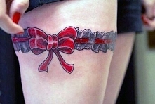 tatuaże damskie podwiązka z kokardą