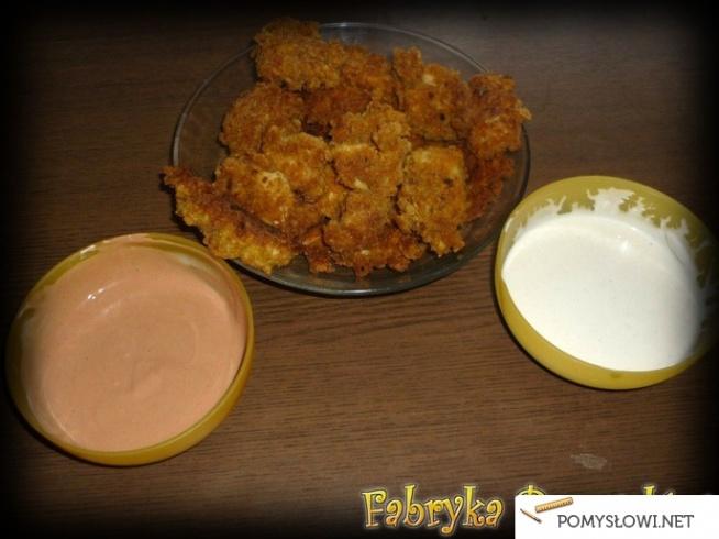 Chrupiące nuggetsy Składniki na 2 pełne talerze: 1 kg piersi z kurczaka 1,5 szklanki mąki  Ok. ¾ szklanki mleka Ok. ¾ -1 łyżeczka curry Ok. ¾ -1 łyżeczka ostrej papryki w proszku 0,5 łyżeczki czosnku granulowanego 2 jajka Mąka do panierki Płatki kukurydziane Sól Pieprz Olej  Przygotowanie: Pierś z kurczaka pokroić w paski o długości mniej więcej 3-4 cm. Posolić i popieprzyć. Wymieszać i odstawić na ok. 20 minut do lodówki. Z mąki, jajek, mleka przygotować gęste ciasto naleśnikowe. Doprawić do smaku curry, papryką w proszku, czosnkiem, solą i pieprzem. Teraz pora przygotować panierkę. Płatki kukurydziane wysypać na ściereczkę. Za pomocą wałka rozkruszyć je. Do miski przesypać płatki, dodać mąkę (tak, aby dominowały płatki). Kawałki kurczaka obtoczyć w cieście, a następnie w panierce. Smażyć na rozgrzanym oleju z obu stron lub na głębokim oleju jak frytki. Składniki na sos czosnkowy: 2 łyżki majonezu 2-3 łyżki jogurtu naturalnego 1 ząbek czosnku Sól Pieprz  Przygotowanie: Majonez wymieszać z jogurtem. Czosnek posiekać. Połączyć zresztą. Posolić i popieprzyć do smaku. Składniki na sos majonezowo- ketchupowy: 2 łyżki majonezu 2 łyżki ketchupu (u mnie pikantny)  Przygotowanie: Składniki mieszamy w proporcji 1:1. Smacznego