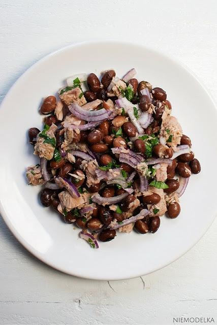 Szybka sałatka z tuńczykiem i czerwoną fasolą Składniki: puszka czerwonej fasoli (zazwyczaj robię z czerwonej, ale na zdjęciu jest akurat z fasoli borlotti) puszka tuńczyka w sosie własnym czerwona cebula 3 łyżki oliwy z oliwek 3 łyżki soku z cytryny 2 łyżki posiekanej natki pietruszki sól, pieprz Sposób przygotowania: 1.Odcedzić tuńczyka i czerwoną fasolę z puszek. Fasolę opłukać zimną wodą. 2.Cebulę pokroić w piórka lub półpiórka. 3.Oliwę zmieszać z sokiem z cytryny i doprawić do smaku solą i pieprzem. To będzie nasz sos. 4.Czerwoną fasolę, tuńczyka, cebulę i pietruszkę polać sosem i dobrze wymieszać.