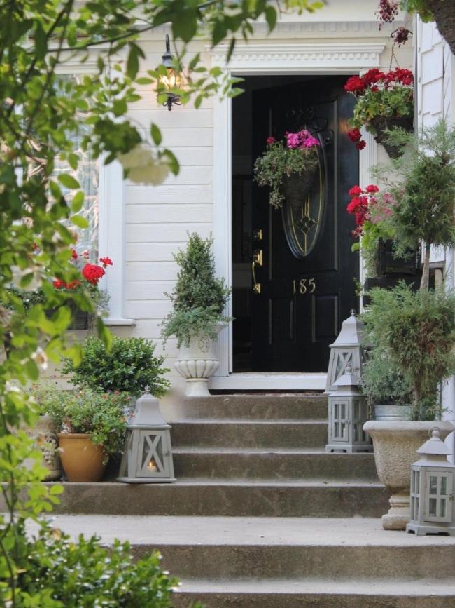 Czarne drzwi, kwiaty, biała elewacja. Design zewnętrza otoczenie domu amerykańskiego. Zobacz jak wygląda typowy dom z USA!