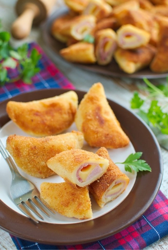 pierożki z szynka i serem z ciasta parzonego . SKŁADNIKI: CIASTO: 1,5 szklanki mąki, 1,5 szklanki mleka, 1,5 łyżki masła, 3/4 płaskiej łyżeczki soli, NADZIENIE: 250g szynki, 200g żółtego sera, DODATKOWO: 2 jajka, Bułka tarta do panierowania, Olej do smażenia PRZYGOTOWANIE: NADZIENIE: Ser kroimy w kostkę, a szynkę w cienkie plasterki. CIASTO: Do garnka wlewamy mleko, dodajemy masło i zagotowujemy. Do miski wsypujemy mąkę i sól, wlewamy gorące mleko. Mieszamy aż składniki się połączą i odstawiamy do przestudzenia. Ciasto wyrabiamy chwilkę, aby nie było grudek, podsypując mąką. Ciasto cienko rozwałkowujemy (3mm) i szklanką wycinamy koła. Na każdym krążku układamy kawałek szynki i kostkę sera i zlepiamy pieroga. Starajmy się dać do środka jak najwięcej farszu. W misce roztrzepujemy jajka. Pierogi maczamy w jajka, a następnie panierujemy w bułce tartej i smażymy na rumiano z obu stron na rozgrzanym oleju. Oleju powinno być sporo. Pierożki podajemy np. z ketchupem ( i/lub majonezem). Są smaczne na ciepło i na zimno.