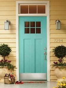 Urocze niebieskie drzwi z górnym doświetlem w pastelowo żółtej elewacji z sid...