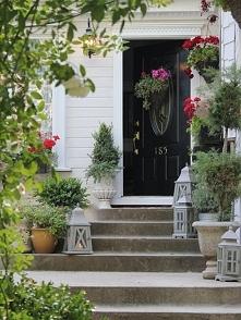 Czarne drzwi, kwiaty, biała elewacja. Design zewnętrza otoczenie domu ameryka...