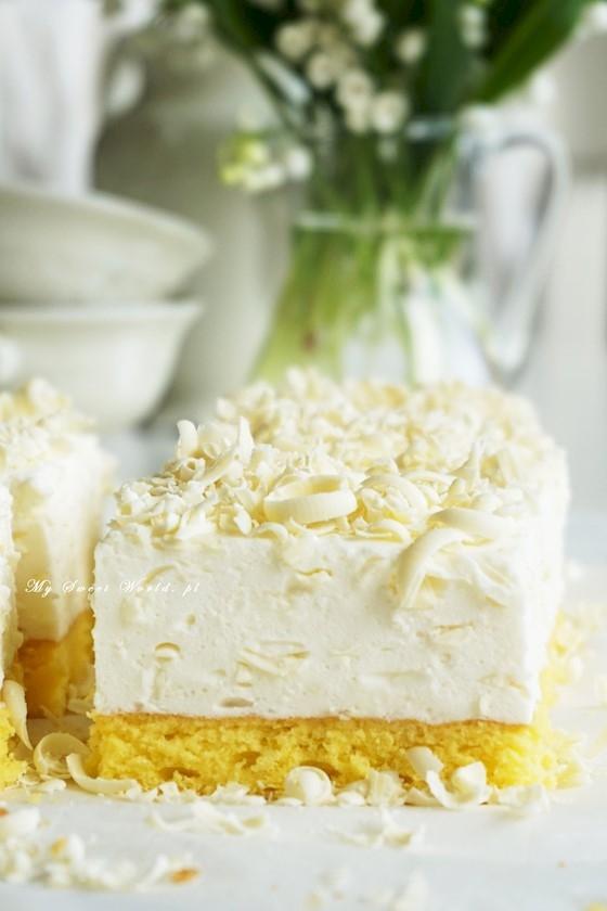"""Ciasto """"Biały puch""""  Składniki na dużą blachę (około 25 na 35 cm):  Na biszkopt: 4 duże jajka 130 g cukru 100 g mąki tortowej 40 g mąki ziemniaczanej szczypta soli do nasączenia: 3/4 – 1 szklanka mleka  Na masę: 2 galaretki cytrynowe + 1 szklanka wrzątku 660 ml śmietanki 30% (użyłm 2 kubki Mlecznej Doliny) 1 opakowanie śnieżki 2 kubki serka Danio waniliowego (po 150g) 300 g jogurtu naturalnego (jeden większy kubek) 2 tabliczki białej czekolady  Upiec biszkopt. Odważyć potrzebne składniki. Piekarnik rozgrzać do 165 ºC.  Białka dokładnie oddzielić od żółtek. Dodać szczyptę soli i ubić mikserem na sztywną pianę (nie dłużej-żeby nie """"przebić"""" białek). Stopniowo dodawać cukier, ubijać aż piana zgęstnieje. Dodać żółtka i dalej ubijać. Na koniec przesiać do masy mąkę i skrobię, następnie wmieszać delikatnie całość wyłączonym mikserem.  Dno blaszki wyłożyć  papierem do pieczenia, boków nie smarować. Przelać pianę biszkoptową do formy i wyrównać. Piec około 40 minut. Wyjąć, upuścić dwukrotnie blaszkę z wysokości kilkudziesięciu cm na przygotowaną deskę (dzięki temu biszkopt nie opada). Wystudzić w temp. pokojowej. Wystudzony biszkopt nasączyć równomiernie mlekiem. Biszkopt przez to ostatecznie będzie nieco cieńszy niż przed nasączeniem, ale wilgotny.  Gdy biszkopt się studzi rozpuścić  galaretki  w szklance wrzątku i wystudzić. W dużym naczyniu ubić śmietankę z dodatkiem śnieżki, aż będzie puszysta, dodać serki homogenizowane, jogurt i zmiksować. Jedną białą czekoladę zetrzeć na tarce (na średnich oczkach) i dodać masy. Na końcu wlać wystudzone, ale nadal płynne galaretki, dokładnie zmiksować. Przelać masę na ostudzony biszkopt, wyrównać i wstawić do lodówki na około 2 godziny. Drugą białą czekoladę zetrzeć na wierzch ciasta."""