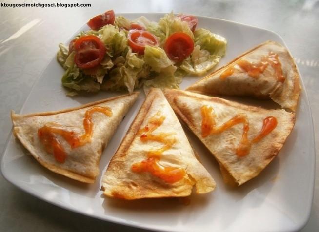 Mini quesadillas czyli tortilla z...tostera :) z farszem pieczarkowo-porowym z kurczakiem i serem SKŁADNIKI 2 placki tortilli 1/2 pora 10 małych pieczarek pół małej piersi kurczaka 5 dag sera żółtego PRZEPIS  1. Kurczaka pokroić w drobną kostkę, doprawić (u mnie przyprawa kebab-gyros), usmażyć. 2. Por pokroić w cienkie plasterki, zeszklić na maśle. 3. Pieczarki przekroić na pół. Dodać do pora i razem udusić do miękkości. Posolić do smaku. Jeśli warzywa puściły za dużo wody, należy ją zredukować lub wylać. 4. Do pieczarek i pora dodać usmażone mięsko i nie zdejmując z ognia wymieszać. Ser zetrzeć na tartce i dodać do reszty, wymieszać (tak, aby składniki się tym serem skleiły). 5. Toster rozgrzać. Położyć 1 placek tortilli i na połowie rozłożyć farsz (jak na zdjęciu), tortillę złożyć na pół, zamknąć pokrywę tostera i piec do zrumienienia ciasta.