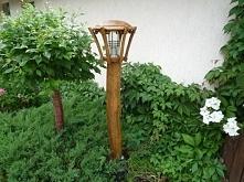 Drewniana lampa ogrodowa, świetnie wpisująca się w zieleń ogrodową