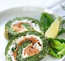 Szpinakowe roladki z łososiem  Składniki:  mrożony szpinak; 400 g łososia w plastrach; 4 jajka; twaróg lub dwa opakowania serków twarogowych; 2 ząbki czosnku; mąka; masło; pieprz, sól. Sposób przygotowania:  Szpinak rozmrażamy na patelni, dodajemy sól, pieprz oraz przeciśnięty czosnek. Gdy szpinak ostygnie, dodajemy do niego żółtka z jajek, a białka ubijamy na sztywno. Ubitą pianę dodajemy do szpinaku i bardzo delikatnie mieszamy, dodajmy dwie łyżki mąki i mieszamy do uzyskania gładkiej konsystencji. Wykładamy na blachę, wyłożoną papierem do pieczenia i zapiekamy w piekarniku przez 15 minut w temperaturze 180 stopni. Po wyjęciu z piekarnika, odstawiamy do przestygnięcia. Smarujemy serkiem twarogowym, rozkładamy płaty łososia, a następnie zwijamy w roladę. Zwijamy ją w folię i wkładamy na kilka godzin, aby zastygła. Następnie kroimy roladę w plasterki.