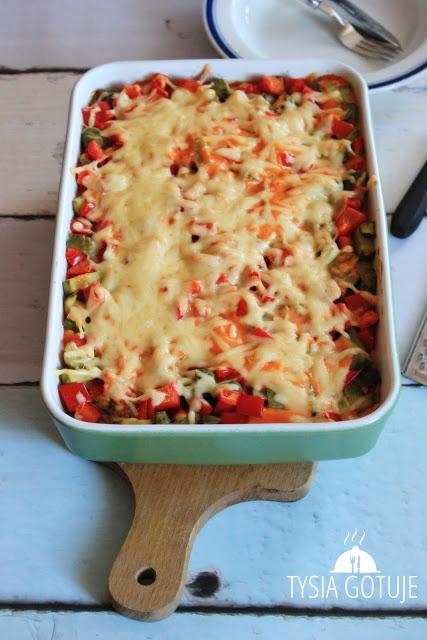 Zapiekanka gyros: Składniki: na ok. 3-4 średniej wielkości porcje naczynie żaroodporne ok. 20 cm x 25 cm ok. 300 g ryżu (2-3 woreczki) ok. 300 g piersi z kurczaka 150 g sera żółtego 1 duża cebula 5-6 średniej wielkości ogórków konserwowych kilka płatów papryki konserwowej 2-3 łyżeczki przyprawy gyros 1-2 łyżki oliwy do smażenia sos: 3 łyżki ketchupu 3 łyżki majonezu 3 łyżki śmietany 12% lub 18% Ryż gotuję do miękkości w osolonej wodzie, cebulę siekam w piórka. Mięso kroję w kostkę o wielkości ok. 1cm x 1cm, przyprawiam dość obficie przyprawą gyros i smażę wraz z cebulą na niewielkiej ilości oliwy. Paprykę kroję w kostkę, ogórki kroję np. w półtalarki. Ser żółty ścieram na tarce o grubych oczkach, wszystkie składniki na sos dokładnie ze sobą mieszam. Naczynie żaroodporne smaruję masłem i układam na dno warstwę ryżu, który smaruję połową sosu. Na ryż wykładam podsmażone mięso wraz z cebulą, które przyprószam 1/3 startego sera żółtego. Następnie układam paprykę i ogórki, równam i smaruję pozostałym sosem. Wierzch zapiekanki przyprószam obficie pozostałym serem żółtym. Całość zapiekam bez przykrycia w piekarniku nagrzanym do 180 stopni C przez ok. 30-40 minut. Zapiekankę po ostygnięciu można schować do lodówki i odgrzać np. następnego dnia, będzie równie dobrze smakować.