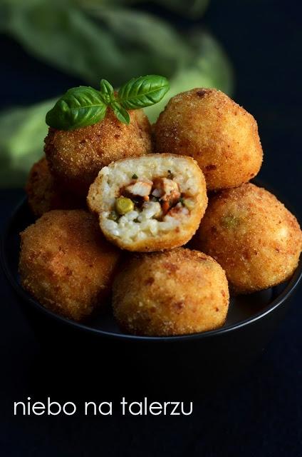 Przekąska na sylwestra. Kulki z ryżu. Włoskie arancini składniki ( na ok. 15 szt) : - 1,5 szklanki ryżu do risotto (np. arborio) - duża cebula lub dwie małe - 3 szklanki bulionu warzywnego lub mięsnego, ew. zwykłej, osolonej wody - 2 łyżki masła lub oliwy z oliwek - 100 g parmezanu, grana padano lub innego sera w tym rodzaju - jajko -sól, pieprz do smaku, ew. szafran lub curry dla koloru, oregano, ostra papryka itp. nadzienie: - ok. 200 g mięsa mielonego (drobiowego, wieprzowego lub wołowego) - 3-4 pieczarki - 3/4 szklanki groszku ( z mrożonki lub puszki) - marchewka - 2 pomidory (mogą być z puszki) lub łyżka przecieru - 2 ząbki czosnku - dwie łyżki siekanej natki pietruszki - kieliszek białego wina (niekoniecznie) - łyżka lub dwie siekanej drobno natki pietruszki - sól - pieprz do panierowania - mąka - tarta bułka - 2 jajka do smażenia: - olej Na dużej patelni lub w dużym, szerokim rondlu rozgrzać masło lub oliwę. Na gorącą wrzucić pokrojoną w kostkę cebulę. Mieszać aż będzie szklista wtedy dodać ryż. Dolać pół szklanki bulionu lub wody, podgrzewać mieszając aż cały płyn zostanie wchłonięty. Dodać kolejne pół szklanki płynu i dalej mieszając czekać aż się wchłonie, tak samo z ostatnią porcją wywaru i kieliszkiem wina. Całość zajmie ok. 20 minut, ryż w tym czasie powinien całkowicie zmięknąć. Dodać starty na drobnej tarce ser, jajko, świeżo zmielony pieprz, dosolić do smaku, dobrze wymieszać. Odstawić do całkowitego ostudzenia. Grzyby drobno pokroić, podsmażyć na niewielkiej ilości tłuszczu na mocno rozgrzanej patelni. Dodać zmiażdżony lub drobno pokrojony czosnek i po krótkiej chwili dorzucić mielone mięso oraz groszek, jeśli z mrożonki. Smażyć aż mięso straci różowy kolor a groszek lekko zmięknie. Ten z puszki dajemy na samym końcu. Dorzucić pokrojone pomidory bez skóry (świeże - bez gniazd nasiennych) i startą na grube wiórki marchewkę. Smażyć ok. 10 - 15 minut by odparował ewentualny płyn. Posolić, posypać świeżo zmielonym pieprzem i dodać natkę pietruszki. Wymi