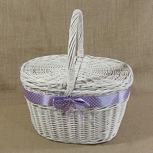 Biały wiklinowy kosz piknikowy zdobiony fioletową wstążką w białe grochy