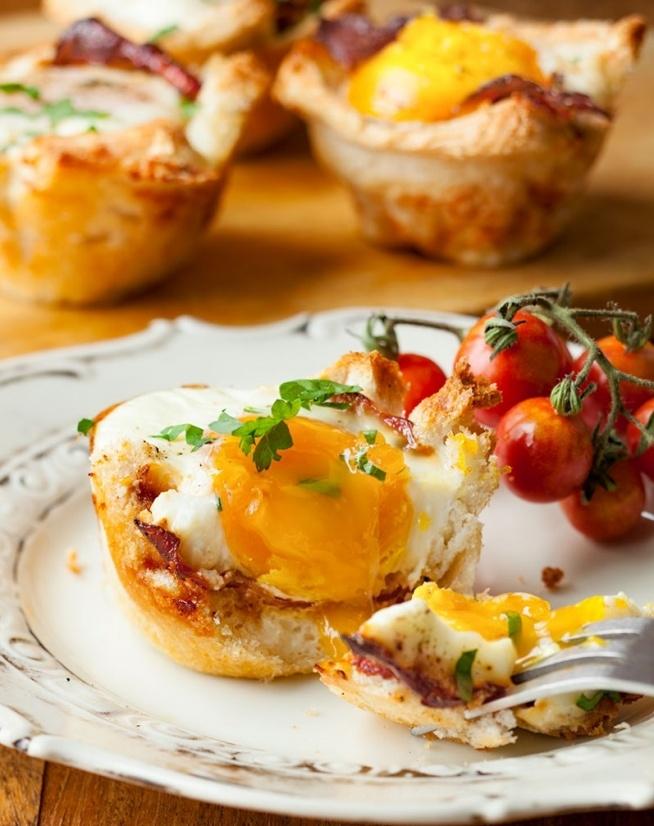 JAJKA ZAPIEKANE W TOSTACH W FORMIE NA MUFFINY SKŁADNIKI: - 50 g masła - 6 kromek pieczywa tostowego - 6 plasterków boczku - 6 jajek - natka pietruszki lub koperek PRZYGOTOWANIE: Piekarnik nagrzać do 200 stopni C. Odkroić skórkę z tostów. Roztopić masło, częścią wysmarować wgłębienia w formie na muffiny, resztą posmarować jedną stronę tostów. Włożyć je do wgłębień posmarowaną stroną do dołu. Plasterki boczku delikatnie obsmażyć na patelni i włożyć do tostów. W środek wbić jajko, doprawić je solą i pieprzem. Wstawić do nagrzanego piekarnika i piec przez około 15 - 17 minut aż białka będą ścięte a żółtka płynno-miękkie. Posypać posiekaną natką, wyjąć na talerzyki i podawać np. z sałatką z pomidorów. WSKAZÓWKI: Zamiast boczku można użyć szynki (bez podsmażania), szynki parmeńskiej lub suszonych pomidorów w wersji wegetariańskiej.