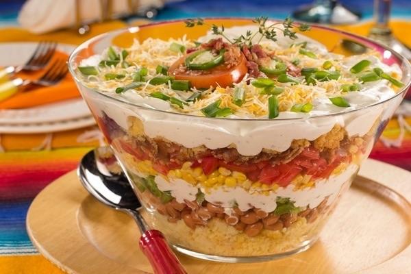 Sałatka Hawajska . Składniki: puszka kukurydzy konserwowej, puszka ananasa, 20 dkg żółtego sera (najlepiej ementaler lub gouda), 15 dkg drobiowej szynki, 2 czerwone cebule, pęczek szczypiorku, mały słoiczek selera konserwowego, 4 łyżki majonezu, sól, pieprz Sposób przygotowania: Ser zetrzeć na tarce o grubych oczkach, szynkę pokroić w drobną kostkę. Odsączyć z zalewy selera, kukurydzę i ananasa, którego należy dodatkowo pokroić w kostkę. Cebulę drobno posiekać. Układać warstwowo wszystkie składniki, przedzielając je warstwami majonezu, doprawionego do smaku solą oraz pieprzem. Szczypiorek drobno posiekać i posypać nim sałatkę. Odstawić na pół godziny do lodówki, po czym podawać. Smacznego :)