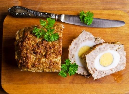Pieczeń rzymska z jajkiem Składniki 1 kg mięsa mielonego (wieprzowego, wieprzowo-wołowego lub z indyka) 1 duża cebula 2 ząbki czosnku 4 łyżki bułki tartej 5 jajek Tymianek, papryka słodka, sól, pieprz Sposób przygotowania Zobacz, jak zrobić pyszną pieczeń rzymską z jajkiem! 1. Do miski wbij jedno surowe jajko. 2. Dodaj do niego mięso mielone, bułkę tartą, oraz przyprawy. 3. Pozostałe jajka ugotuj na twardo. 4. Posiekaj cebulę w drobną kostkę. 5. Cebulę oraz przeciśnięty przez praskę czosnek dodaj do mięsa. Wyrób rękami całość na jednolitą masę. 6. Rozgrzej piekarnik do 190 stopni. 7. Wyłóż keksówkę papierem do pieczenia. 8. Na jej dnie umieść jedną trzecią masy mięsnej. 9. Obierz ugotowane jajka, obetnij z nich spód i czubek, tak, żeby odsłoniły się żółtka. Jajka umieść w foremce na mięsie, na środku, w rzędzie. 10. Dodaj resztę mięsa, tak aby przykryć jajka ze wszystkich stron. 11. Wstaw do piekarnika i piecz przez ok. 50 minut. 12. Można jeść na ciepło, jako główny składnik obiadu, jak również na zimno, na przykład na kanapkach.