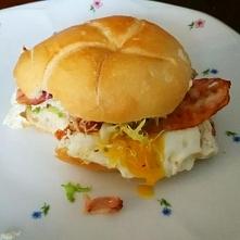 Burger śniadaniowy - jajko sadzone na bekonie w bułce z dodatkiem sałaty i ki...
