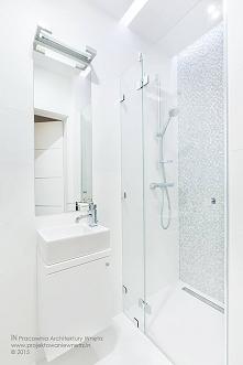 Malutka łazienka cała w bieli. Elementem dekoracyjnym jest piękna szklana moz...