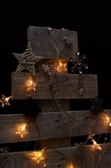 Choinka własnoręcznie wykonana z palety, pomalowana na biało i przetarta. Choinka ozdobiona lampkami i bombkami choinkowymi.
