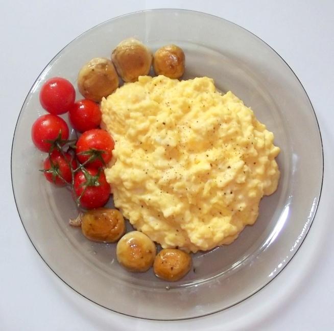 Dzień Dobry wszystkim. Dziś Chciałbym wam pokazać jak podbić serce Kobiety rano. Przepis jest prosty perfekcyjne śniadanie podane do łóżka z dobrze zrobioną Kawą :) Więc Zaczynajmy  Składniki do naszej jajecznicy: 3 Jajka 2 łyżki masła 1 Crème fraîche (można użyć śmietany 18%) Kilka Pieczarek Pomidorki koktajlowe Sposób przygotowania   Na Patelni rozgrzewam oliwę. Myję warzywa. Odrywam nóżki pieczarek. Na patelnie kładę pomidorki koktajlowe i kapelusze pieczarek, i zostawiamy na wolnym ogniu. Na zimna patelnie( ja używam rondelka) wbijam jajka i dodaje masło. Stawiam na ogniu i mieszam ważne jest aby cały czas mieszać. Zdejmuje z gazu od czasu do czasu ponieważ nie chcemy żeby patelnia zbyt mocno się nagrzała oczywiście mieszam cały czas. Gdy jajko się już zetnie, zdejmuję z gazu i dodaję śmietanę.Przyprawiam solą i pieprzem na koniec ponieważ gdy dodamy sól na początku jajecznica zrobi się wodnista i nie uzyskamy odpowiedniej konsystencji. Żeby seksić jajecznicę dodaje szczypiorek. Jajecznice Wykładam na talerz, obok układam pomidorki i pieczarki. Do jajecznicy polecam zrobić grzanki świetnie pasują do jajecznicy. Zainspirowałem się przepisem Pana Gordona Ramsaya. Życzę smacznego :)