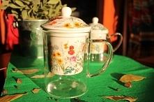 Elegancki kubek z zaparzaczem z porcelany ozdobionej motywem ziół i polnych kwiatów.