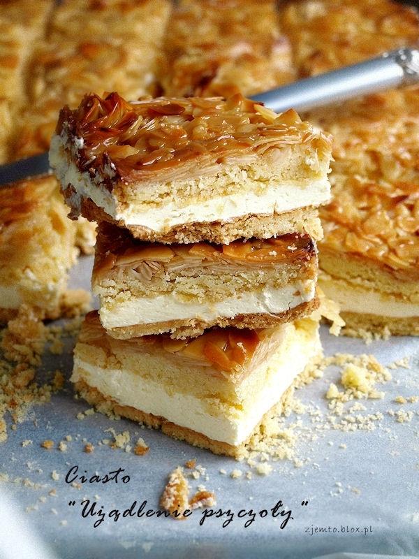 """Ciasto """"Użądlenie pszczoły""""  Składniki: ( na formę o wym. 22 x 32cm )  kruche ciasto:  400 g mąki tortowej 250 g zimnego masła 2/3 szklanki cukru pudru 2 żółtka 1 łyżka kwaśnej śmietany 1 łyżeczka proszku do pieczenia  krem budyniowy: (można zastąpić ulubioną masą karpatkową)  6 żółtek 2 szklanki mleka 220 ml śmietanki 30% 150 g cukru 1 łyżeczka cukru z prawdziwą wanilią (można zastąpić cukrem wanilinowym) 1 pełna łyżka mąki pszennej 3 pełne łyżki mąki ziemniaczanej 220 g masła w temp. pokojowej karmelizowane migdały:  70 g cukru pudru 70 g miodu 70 g śmietanki 30% 100 g masła 200 g płatków migdałów  Sposób wykonania:  Mąkę z proszkiem do pieczenia przesiać na stolnicę. Dodać pokrojone w kostkę masło, cukier, żółtka i śmietanę. Wszystko siekać nożem, a następnie szybko zagnieść jednolite ciasto. Podzielić je na 2 części, lekko spłaszczyć, zawinąć w folię i wstawić na 1 godzinę do lodówki.  W czasie, gdy ciasto się chłodzi przygotować masę migdałową.  W garnuszku z grubym dnem umieścić miód, śmietankę, cukier i masło. Podgrzewać do połączenia składników. Dodać płatki migdałów. Wymieszać i doprowadzić do wrzenia. Gotować razem ok. 1 minuty. Odstawić z palnika.  Dno formy wyłożyć papierem do pieczenia. Cienko rozwałkować pierwszy kawałek ciasta. Wyłożyć nim spód formy. Ponakłuwać widelcem. Wstawić do nagrzanego piekarnika. Piec w temp. 180 C ok. 15 minut, aż ciasto ładnie się zezłoci.  Drugi placek rozwałkować, wyłożyć nim dno formy, ponakłuwać widelcem. Wstawić do nagrzanego piekarnika. Podpiec 8 minut. Ciasto wyjąć, wyłożyć masę migdałową i piec kolejne 10-15 minut. Gdyby wierzch migdałowy za bardzo się rumienił, przykryć folią aluminiową.  Przygotować krem:  Żółtka, obie mąki i pól szklanki mleka zmiksować. Pozostałe mleko zagotować z cukrem i cukrem z wanilią. Dodać śmietankę, wymieszać i zagotować. Teraz dodać wcześniej przygotowane żółtka z mąkami. Wszystko energicznie mieszać, doprowadzić do wrzenia i gotować około minuty. Powinien powstać aksamitny budyń. Garnu"""