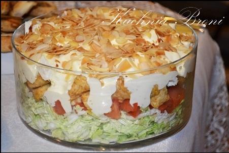 """Sałatka warstwowa z serkiem feta  Składniki:  1/2 kapusty pekińskiej  5 pomidorów  500g piersi z kurczaka  Ser feta """"Fawita"""" 270g z """"Mlekowita""""  10dkg Płatków migdałów  Sos czosnkowy:  1 mały majonez  1 mała śmietana 18%  2 ząbki czosnku  sól,pieprz  Mięso z kurczaka pokroić w drobną kostkę, usmażyć na patelni z dodatkiem przyprawy do drobiu, odsączyć na papierowym ręczniku i odstawić do wystygnięcia. Kapustę pekińską pokroić w paseczki,pomidory w drobną kostkę, a ser feta  w kostkę 1cm na 1cm. Migdały zrumienić na suchej  patelni (bez dodatku tłuszczu).  Przygotować sos czosnkowy: Wszystkie składniki sosu połączyć ze sobą i doprawić.  Układać kolejno w szklanym naczyniu:  kapusta  pomidory  pierś z kurczaka  ser feta  polać wszystko przygotowanym sosem czosnkowym i posypać uprażonymi migdałami.Odstawić na 2-3 godziny."""