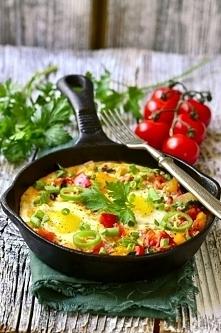 SHAKSHUKA Składniki: 2 jajka 3 pomidory lub 1 puszka pomidorów krojonych w puszce 1/2 czerwonej papryki 1/2 żółtej papryki 3 łyżki koncentratu pomidorowego 1 cebula 2 ząbki czosnku 1/2 łyżeczki kuminu 1/2 łyżeczki ostrej papryki 1/2 łyżeczki słodkiej papryki sól pieprz oliwa z oliwek Do podania: siekana natka pietruszki siekany szczypiorek siekana ostra, zielona papryczka Przygotowanie: Warzywa dokładnie myjemy i osuszamy. Cebulę wraz z czosnkiem drobno siekamy, paprykę kroimy w kostkę, a pomidory zalewamy wrzątkiem, obieramy ze skórki i również kroimy w kostkę. Na patelni rozgrzewamy oliwę z oliwek, podsmażamy cebulę oraz czosnek, a następnie dodajemy paprykę, pomidory i wszystkie przyprawy. Gotujemy do momentu uzyskania gęstego sosu, dodajemy koncentrat pomidorowy i doprawiamy do smaku. Warzywa na patelni odgarniamy za pomocą łyżki i w powstałe miejsca wbijamy jajka, które zetną się w gotującym sosie. Całość możemy przykryć, ale uważajmy aby żółtka się nie ścięły. Podajemy od razu z siekanymi ziołami i ulubionym pieczywem.