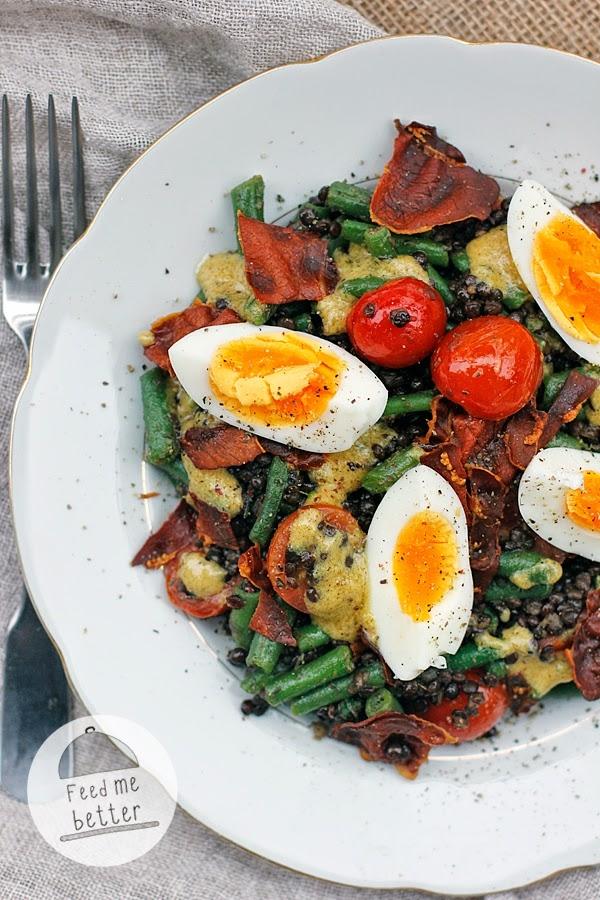 SAŁATKA Z SOCZEWICĄ I JAJKIEM przepis na 2 porcje 120 g czarnej soczewicy 4-6 plasterków szynki parmeńskiej 2 jajka 200 g fasolki szparagowej 10 pomidorków cherry 1 łyżka oliwy 1 ząbek czosnku sól morska świeżo mielony pieprz dressing: 1,5 łyżki musztardy sarepskiej 1 łyżka octu 1 łyżka oliwy z oliwek 1 łyżka mleka świeżo mielony pieprz Soczewicę gotujemy według instrukcji na opakowaniu (można ją wcześniej namoczyć przez noc, jednak nie jest to konieczne). Jajka gotujemy na twardo lub półtwardo (ja wkładam je do wrzącej wody i gotuję 7-8 minut). Fasolkę krótko gotujemy, a następnie odcedzamy i natychmiast schładzamy w lodowatej wodzie. Szynkę parmeńską rozkładamy na blaszce wyłożonej papierem do pieczenia i zapiekamy przez około 5-6 minut w 200 stopniach, aby otrzymać czipsy. Na patelni rozgrzewamy oliwę i wrzucamy przekrojone na połówki pomidorki cherry. Smażymy je często mieszając przez 2 minuty, po tym czasie dodajemy posiekany ząbek czosnku i fasolkę, po kolejnych dwóch minutach ugotowaną soczewicę. Smażymy chwilę, aby wszystkie składniki były ciepłe. Przekładamy na talerze, posypujemy czipsami z szynki parmeńskiej i rozkładamy przekrojone na ćwiartki jajka. Polewamy dressingiem (wystarczy dokładnie wymieszać wszystkie składniki).