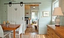 Piękne, rustykalne wnętrze z białymi drzwiami przesuwnymi.