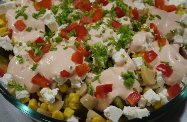 SAŁATKA Z FETĄ  Sałatka imprezowa na zimę z produktów całorocznych, tj. zapuszkowanych:-) Z pysznym sosem majonezowo-ketchupowym odchudzonym jogurtem śródziemnomorskim.  Składniki: - opakowanie fety - puszka kukurydzy - słoik pieczarek - 1/2 słoika ogórków konserwowych - 1/2 czerwonej papryki do dekoracji (surowa lub ze słoika) - zielenina do dekoracji (szczypiorek lub czubrica) Sos: - 2 łyżki majonezu - 3 łyżki ketchupu - 3 łyżki jogurtu śródziemnomorskiego Na durszlak przełożyć kukurydzę, pieczarki, ogórki oraz paprykę i dobrze odsączyć (można też użyć papierowego ręcznika kuchennego). Pieczarki, ogórki i paprykę pokroić na dość dużą kostkę. W kostkę pokroić także fetę.  W dużym kubku wymieszać składniki na sos. Podane wyżej proporcje pozwolą uzyskać gęstą konsystencję w kolorze łososiowym.  Na duży półmisek wyłożyć kolejno 2 warstwy kukurydzy, pieczarek, ogórków, papryki i fety Każdą warstwę polać sosem. Wierzch udekorować papryką i zieleniną. Sałatka nadaje się od razu do podania.