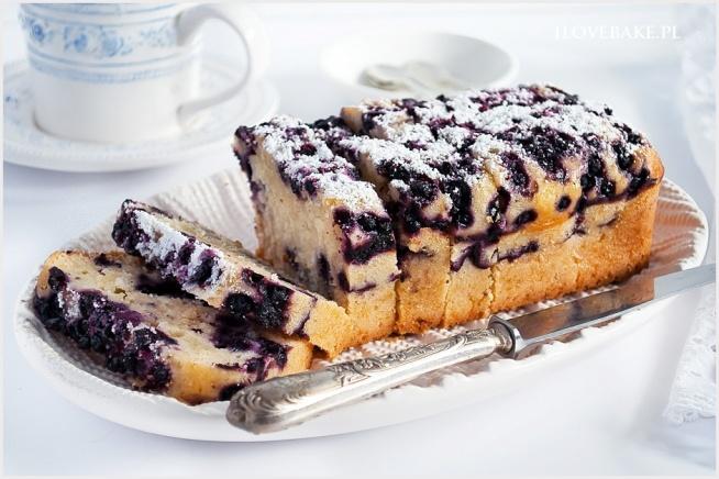 KOKOSOWE CIASTO Z JAGODAMI  SKŁADNIKI NA CIASTO:  2 szklanki mąki tortowej 1/2 szklanki wiórków kokosowych 3/4 szklanki cukru 2 łyżeczki proszku do pieczenia 170 g masła, roztopionego 2/3 szklanki mleka np. kokosowego 2 łyżki jogurtu greckiego, temp. pokojowa 2 jajka, duże 1 łyżeczka ekstraktu z wanilii lub esencji DODATKOWO:  1 szklanka jagód, świeżych lub mrożonych * 1 szklanka o pojemności 250 ml.  Mąkę przesiewamy razem z proszkiem do pieczenia. Następnie dodajemy wiórki. Jajka miksujemy z cukrem do lekkiego spienienia, nie dłużej. Następnie zmniejszamy obroty miksera do minimum i powoli wlewamy roztopione masło o temp. pokojowej, jogurt, ekstrakt, mleko i na koniec w kilku porcjach suche składniki. Formę o wymiarach 20×10 lun nieco większą wykładamy papierem do pieczenia lub używamy silikonowej. Przekładamy połowę ciasta i oprószamy połową jagód (mrożonych nie rozmrażamy, a jedynie obtaczamy w łyżeczce mąki ziemniaczanej). Przykrywamy drugą połową ciasta i ponownie oprószamy pozostałymi jagodami. Pieczemy w temp. 170 C przez około 50-60 min. do tzw. suchego patyczka. Podajemy oprószone cukrem pudrem.
