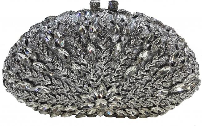 Cudownie błyszcząca torebka, ręcznie zdobiona kryształkami w wielu kształtach i rozmiarach. Kryształki ułożone w wzór kwiata i odchodzących od niego liści tworzą niesamowity wzór. Torebka cała zdobiona, posrebrzane okucie i zapięcie wysadzone malutkimi kryształkami.