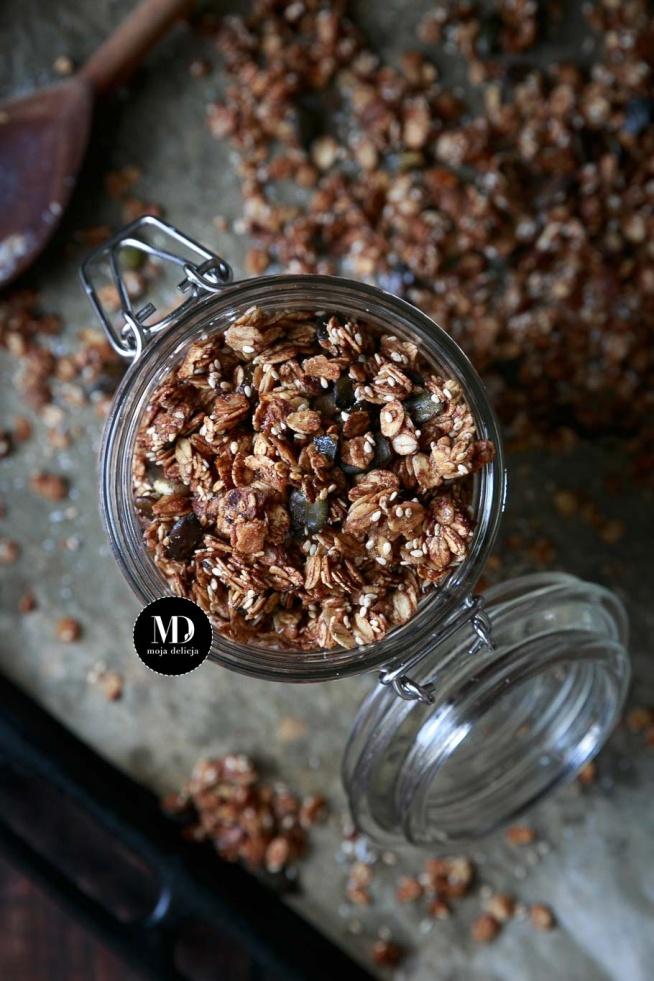 Granola pieczona w piekarniku. Z sezamem, pestkami dyni i cynamonem. Słodzona miodem i syropem z agawy. Prosta i szybka w przygotowaniu.