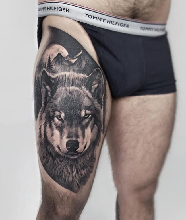 wilk tatuaż na udzie mężczyzny