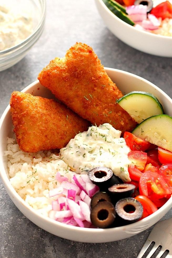 Filety panierowane serwowane z sosem ogorkowym, pomidorami, oliwkami i ryzem.