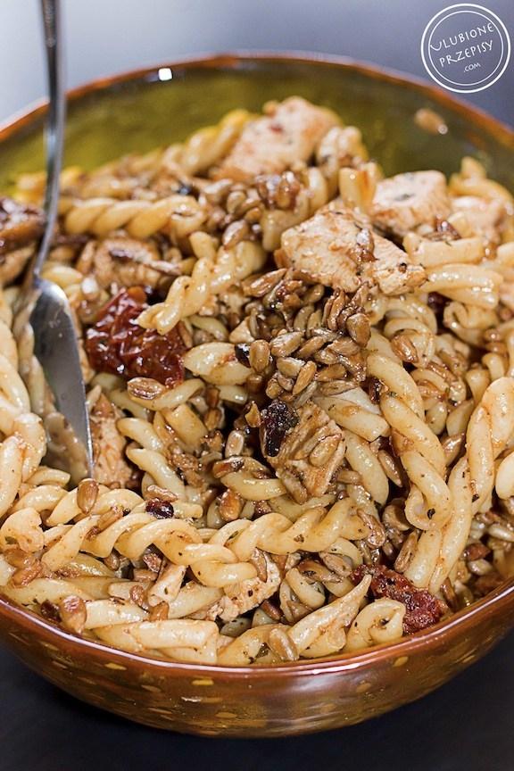 Sałatka makaronowa z kurczakiem, suszonymi pomidorami i ziarnami słonecznika. Liczba porcji: 2-3 Składniki 200 g makaronu 500 g piersi z kurczaka ok. 10 kawałków suszonych pomidorów w oleju 2 ząbki czosnku 8 łyżek nasion słonecznika 1½ łyżeczki ziół prowansalskich ½ łyżeczki słodkiej papryki sól pieprz oliwa Sos: 1 łyżeczka ziół prowansalskich 1 łyżka ketchupu 1 łyżeczka sosu sojowego 1 ząbek czosnku lub czosnek granulowany 1-2 łyżki oleju z suszonych pomidorów (bez octu) opcjonalnie: 1 łyżeczka musztardy Wykonanie Makaron (dowolny, ale gruby) ugotować al dente w osolonej wodzie. Odcedzić i polać zimną wodą. Przestudzić. Kurczaka pokroić w drobną kostkę. Posypać solą, pieprzem, ziołami prowansalskimi i papryką. Dodać przeciśnięty przez praskę czosnek. Kurczaka dokładnie obtoczyć w przyprawach. Kurczaka usmażyć na oliwie z oliwek. Nie przesuszyć go. Słonecznik wrzucić na suchą patelnie i cały czas mieszając zarumienić go, na małym ogniu - smażyć około 8 minut. Uważać, aby słonecznik się nie przypalił ponieważ stanie się gorzki. Kurczaka wymieszać z makaronem i prażonym słonecznikiem. Dodać pokrojone suszone pomidory. Wszystkie składniki na sosik wymieszać i dodać do sałatki. Sałatkę dobrze wymieszać i doprawić do smaku solą i pieprzem. Ja zamiast świeżego czosnku dodałam granulowany - jest jednak subtelniejszy w smaku. Sałatkę wstawić do lodówki, aby się schłodziła.