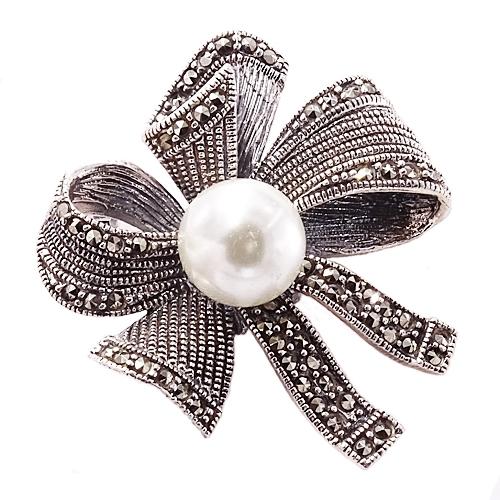Pomysł na prezent. szukaj na braccatta.com Efektowna, duża broszka, wykonana ze srebra, wysadzanego lśniącymi markazytami z centralnie osadzoną, ogromną perłą. Broszka ma kształt fantazyjnie zawiązanej kokardy.  Ozdobna i elegancka.