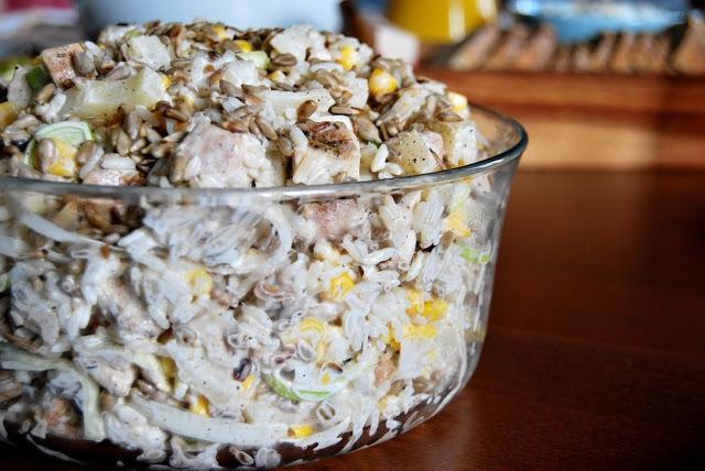 dniki: 200 g białego ryżu; 500 g filetu z piersi kurczaka; Puszka kukurydzy konserwowej (waga netto, po odcedzeniu 285 g); Puszka ananasa w plastrach, w syropie (waga netto 320 g); Biała część średniego pora; 200 g łuskanych ziaren słonecznika; 2 czubate łyżki majonezu; 2 czubate łyżki kwaśnej, gęstej śmietany 18%; 1 łyżka przyprawy do gyrosa; Olej do podsmażenia kurczaka;  Sól; Pieprz.                          Sposób przygotowania: Ryż ugotować zgodnie z przepisem na opakowaniu. Odcedzić. Wystudzić. Przełożyć do miski. Piersi z kurczaka umyć, osuszyć, oczyścić z błon i pokroić w kostkę. Przełożyć do miseczki i oprószyć przyprawą do gyrosa. Smażyć, z obu stron, na złoty kolor, na rozgrzanym na patleni oleju. Wystudzić. Dodać do miski z ryżem. Wymieszać. Ananasa odcedzić z zalewy. Pokroić w kostkę. Dodać do sałatki. Pora umyć, osuszyć, pokroić w cienkie plasterki. Dodać do sałatki. Wymieszać. Słonecznik uprażyć na suchej (tj. bez dodatku tłuszczu) patelni, na złoty kolor. Wystudzić. Dodać do sałatki. Do sałatki dodać majonez i śmietanę. Wymieszać. Sałatkę przyprawić solą i pieprzem do smaku. Wymieszać. SMACZNEGO!