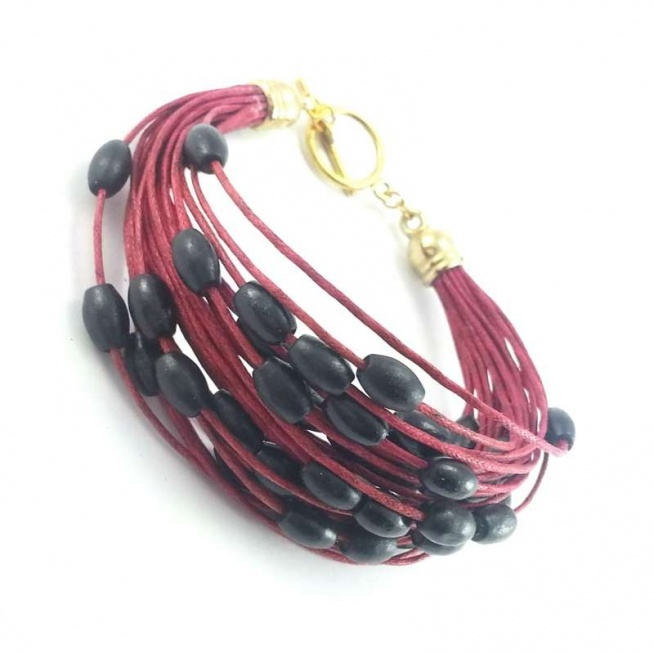 Bransoletka ze sznurka w kolorze bordo z czarnymi drewnianymi koralikami i złotym zapięciem.