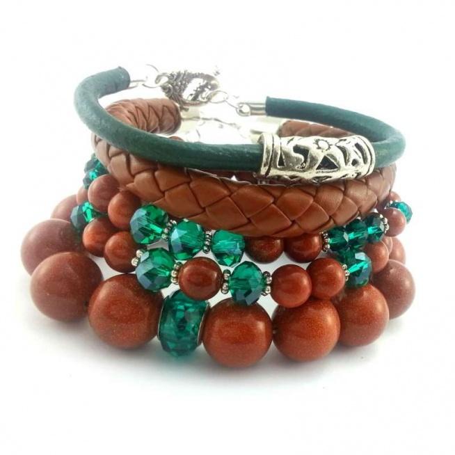 ZESTAW BRANSOLETEK 5W1 PIASEK PUSTYNI ZE SZMARAGDOWYM KRYSZTAŁEM Komplet pięciu bransoletek wykonanych ręcznie. Można je nosić razem lub osobno. Trzy bransoletki z kamienia piasku pustyni o wielkości 14, 8, 6 mm z kryształami szklanymi w kolorze szmaragdowym o wielkości 14,8,6 mm . Zielona bransoletka z rzemienia ze skory naturalnej o grubości 5 mm z zapięciem i koralikiem bali. Ruda bransoletka z rzemienia ze skóry ekologicznej o grubości 10 mm z zapięciem w kształcie serduszka i łańcuszkiem do regulacji. Elementy metalowe w kolorze srebrnym.  Bransoletki będą pasowały na nadgarstek 15,16 cm średnicy.