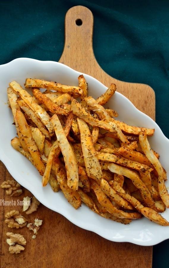 Selerowe Frytki 1 seler korzeniowy 2 łyżki oleju lub oliwy z oliwek 1/2 łyżeczki soli 1/2 łyżeczki słodkiej papryki 1/2 łyżeczki oregano szczypta chilli świeżo zmielony pieprz Selera obieramy (będzie nam potrzebny ostry nóż), kroimy w plastry i następnie w dość cienkie paski. W misce mieszamy ze sobą olej i przyprawy. Wrzucamy do niej pokrojonego selera i dokładnie mieszamy, by frytki pokryły się przyprawami. Całość przekładamy na wyłożoną papierem do pieczenia blachę i rozkładamy tak, by frytki (w miarę możliwości) stanowiły jedną warstwę. Wstawiamy do piekarnika i pieczemy w 180 stopniach przez około 30-40 minut. Smacznego!