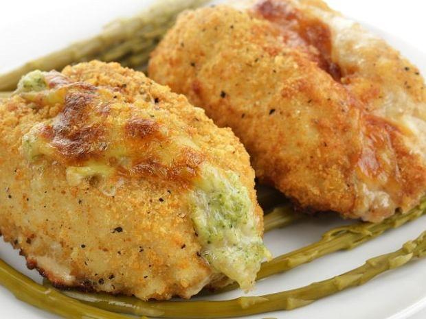 Piersi z kurczaka z farszem brokułowo-serowym i boczkiem Składniki: 2 podwójne piersi z kurczaka 1 mały brokuł (może być także paczka mrożonego) 4 łyżki parmezanu 1ząbek czosnku kilka plasterków żółtego sera (najlepiej gouda) kilka plasterków wędzonego boczku sól i pieprz do smaku 1 jajko 2 łyżki mąki bułka tarta (około0.5-1 szklanka) olej do smażenia Sposób przygotowania: Brokuła podziel na różyczki, podobnie jak kalafiora i ugotuj w osolonej wodzie do miękkości (powinien być naprawdę miękki, nawet lekko się rozpadać). Ostudź i zmiksuj z parmezanem (niezbyt drobno), a następnie dopraw do smaku solą i pieprzem. Piersi z kurczaka umyj, oczyść i podziel na części Rozbij na grubość około 0,5 cm i oprósz solą i pieprzem. Na każdym płacie mięsa układaj najpierw boczek, później ser, a następnie masę brokułową. Zwijaj roladki, starając się, aby farsz nie wyleciał (możesz spiąć wykałaczką). Obtaczaj w mące, roztrzepanym jajku oraz tartej bułce. Smaż na rozgrzanym oleju na złoty kolor. Do bułki tartej możesz dodać ulubione zioła - danie będzie wtedy bardziej aromatyczne.