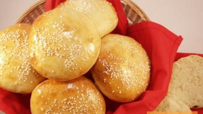 """Bułeczki hamburgerowe – idealne krok po kroku  czas: ok. 2 h (wraz z wyrastaniem i pieczeniem)  liczba porcji: 12 bułek Składniki: 680 g mąki pszennej (typ 480) 200 ml mleka ok. 200 ml wody 2 łyżeczki cukru 7 g drożdży suchych lub 14 g świeżych 2 łyżki masła (rozpuścić w rondelku) 1 łyżeczka soli plus: jajko do posmarowania sezam KROK 1: Do miski wkładam wszystkie składniki na bułeczki. Jeśli używam świeżych drożdży, to je po prostu wkruszam, a gdy suchych, to je wsypuję. Masło rozpuszczam w rondelku, zanim dodam do reszty. Wszystko mieszam, a następnie przekładam na stolnicę i wyrabiam. Ciasto dość łatwo się wyrabia, gdyby jednak było oporne, to troszkę można podsypać mąką. KROK 2: Ciasto wkładam do miski, przykrywam folią spożywczą (tak troszkę nieszczelnie), a następnie ściereczką i odstawiam w ustronne miejsce na 1 h, aby wyrosło. Oczywiście, można tylko ściereczką, po prostu z moich obserwacji wynika, że nie wysycha i jakoś mu lepiej. KROK 3: [na zdjęciu po 1 h wyrastania]. Wyjmuję wyrośnięte ciasto, chwilkę wyrabiam, a następnie dzielę na 12 części – tyle, ile bułek. KROK 4: Z każdej części formuję kulkę. Ja zbieram brzegi i podwijam tak, jakbym łączyła sakiewkę. Dzięki temu, bułeczki będą równe i ładnie naprężone. Następnie spłaszczam je na placuszki. Nie bójcie się spłaszczać, one potem i tak wyjdą wyrośnięte. KROK 5: Odstawiam pod ściereczką na 40 minut, by podrosły. KROK 6: Wyrośnięte bułki leciutko spłaszczam, ale leciutko. Smaruję rozkłóconym jajkiem i posypuję sezamem. Wstawiam do nagrzanego do 200°C piekarnika i piekę przez 15 minut. Zaraz po wyjęciu bułeczki będą miały lekko sztywną powłoczkę, ale gdy chwilkę """"odtajają"""", to będą mięciutkie, więc nie martwcie się. Bułeczki najlepsze są w dniu pieczenia, ale potem przez kolejne 2–3 dni można je łatwo odświeżyć. Wystarczy skropić delikatnie wodą każdą bułeczkę i wstawić na 1–2 minuty do gorącego (na przykład nagrzanego do 150°C) piekarnika. Gotowe."""