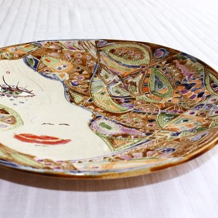 Ręcznie wykonany z gładkiej gliny jasny talerz - Zodiak Strzelec. Wypalony dwukrotnie. Szkliwo na większości powierzchni różnokolorowe. Powierzchnia talerza zewnętrzna szkliwiona jednorodnym pomarańczowym szkliwem. Kolorowe szkliwienie na wzorach wykonanych igłą. Ręcznie wykonana praca, naturalna z wyrytym graficznym obrazkiem. Świetnie prezentuje się na drewnianym stole, lub na jasnych powierzchniach. Polecam serdecznie!   WYMIARY:   - średnica ok. 27 cm