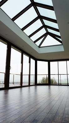 Za dnia wnętrze pomieszczenia doświetlone jest ogromnymi przeszkleniami, za t...
