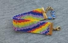 Barwna bransoletka w stylu BOHO z koralików szklanych, wykonana ręcznie techniką tkania na krośnie. Kontrastujące kolory, niektóre matowe, inne połyskujące, układając się w kszt...