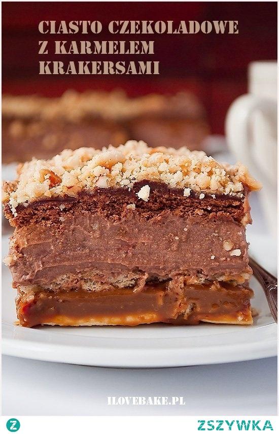 Ciasto czekoladowe z karmelem (bez pieczenia) - I Love Bake SKŁADNIKI NA CIASTO: 2 paczki krakersów, solonych 2 paczki herbatników, kakaowych 1 puszka kajmaku ok. 500 g 100 g orzeszków ziemnych, zmielonych SKŁADNIKI NA KREM CZEKOLADOWY: 800 ml mleka 2 budynie czekoladowe (40g), proszek 4 łyżki cukru 250 g masła, temp. pokojowa 2 łyżki kremu czekoladowego np. nutella 2 łyżki masła orzechowego (niesolone) SKŁADNIKI NA POLEWĘ CZEKOLADOWĄ: 90 ml śmietanki kremówki 30% 100 g gorzkiej czekolady Krakersy układamy w blaszce o wym. 24×24 cm. Rozprowadzamy na nich równomiernie podgrzany wcześniej kajmak. Przykrywamy drugą warstwą krakersów. 400 ml mleka zagotowujemy razem z cukrem. W pozostałym leku rozpuszczamy przesiany proszek budyniowy. Cały czas mieszając wlewamy do gorącego mleka. Podgrzewamy, aż masa będzie dosyć mocno gęsta. Owijamy folią i zostawiamy do całkowitego wystudzenia. Masło przez chwilę ucieramy, następnie dodajemy po łyżce ostudzonego budyniu. Na koniec miksujemy z kremem czekoladowym oraz masłem orzechowym. Na krakersy wykładamy krem czekoladowy i przykrywamy herbatnikami (można je lekko nasączyć np. likierem lub mocną herbatą). Kremówkę mocno podgrzewamy, następnie wrzucamy kawałki połamanej czekolady i zostawiamy na 2-3 min. Mieszamy i polewamy równomiernie herbatniki. Przykrywamy zmielonymi orzechami. Wkładamy do lodówki na całą noc.