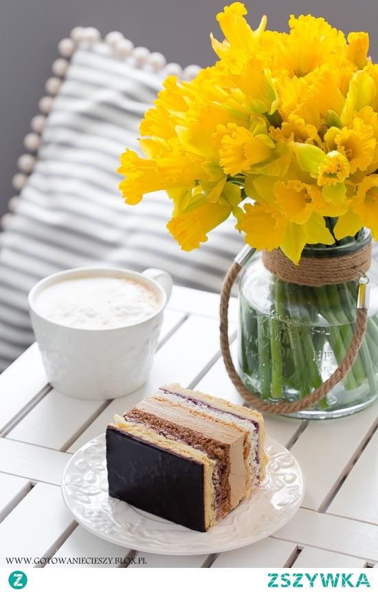 Ciasto Wielkanocne   Jeśli macie ochotę, do masy kawowej możecie dodać wiśnie z nalewki. Z pewnością wpłyną one pozytywnie na smak ciasta Składniki na formę o wymiarach 25x20 cm (wymiar dna)  Ciasto kruche:  * 420 g mąki tortowej * 5 żółtek * 250 g masła * 90 g cukru pudru * 2/3 łyżeczki proszku do pieczenia  * 2 łyżki zimnej wody  Dodatkowo:  * 1 słoiczek konfitury z czarnej porzeczki  Beza kokosowa:  * 4 duże białka * 2 szklanki wiórków kokosowych * 140 g cukru * 1/3 łyżeczki proszku do pieczenia * 1 łyżka mąki  Warstwa orzechowa: * 4 jajka * 180 g cukru * 180 g zmielonych orzechów włoskich * 1 łyżeczka kawy mielonej (nie rozpuszczalnej) * 1/2 łyżeczki proszku do pieczenia  Krem kawowy: * 300 g bardzo miękkiego masła (najlepiej wyjętego z lodówki poprzedniego dnia) * 2 jajka * 2 żółtka * 200 g cukru pudru  * 4 łyżeczki miałkiej, delikatnej kawy rozpuszczalnej * 2 x 50 ml wody    Polewa:  * 50 g masła * 10 łyżek mleka * 1/2 szklanki cukru pudru * 3 kopiaste łyżki gorzkiego kakao  Ciasto  Z wymienionych składników zagniatamy gładkie, jednolite ciasto i dzielimy je na dwie równe części (najprostszym i najszybszym sposobem na przygotowanie kruchego ciasta jest zmiksowanie składników w malakserze, jeśli takowy posiadacie).  Pierwszą część ciasta wałkujemy i wykładamy nim spód formy (wyłożony wcześniej papierem do pieczenia). Na cieście rozsmarowujemy połowę konfitur i przygotowujemy bezę kokosową.  Białka ubijamy z cukrem na bardzo sztywną pianę, a następnie dodajemy do niej wiórki kokosowe wymieszane z mąką i proszkiem do pieczenia. Miksujemy jeszcze chwilę, do chwili połączenia się składników. Bezę przekładamy na ciasto, wyrównujemy wierzch i wstawiamy do nagrzanego do 180 stopni. Pieczemy około 40 minut (ostatnie 7 minut podpiekałam tylko spód).  Drugą częścią ciasta wykładamy drugą formę, smarujemy je pozostałymi konfiturami i przygotowujemy pianę orzechową.  Jajka ubijamy z cukrem przez około 8 minut, do czasu uzyskania jasnej, puszystej masy, do której następnie 